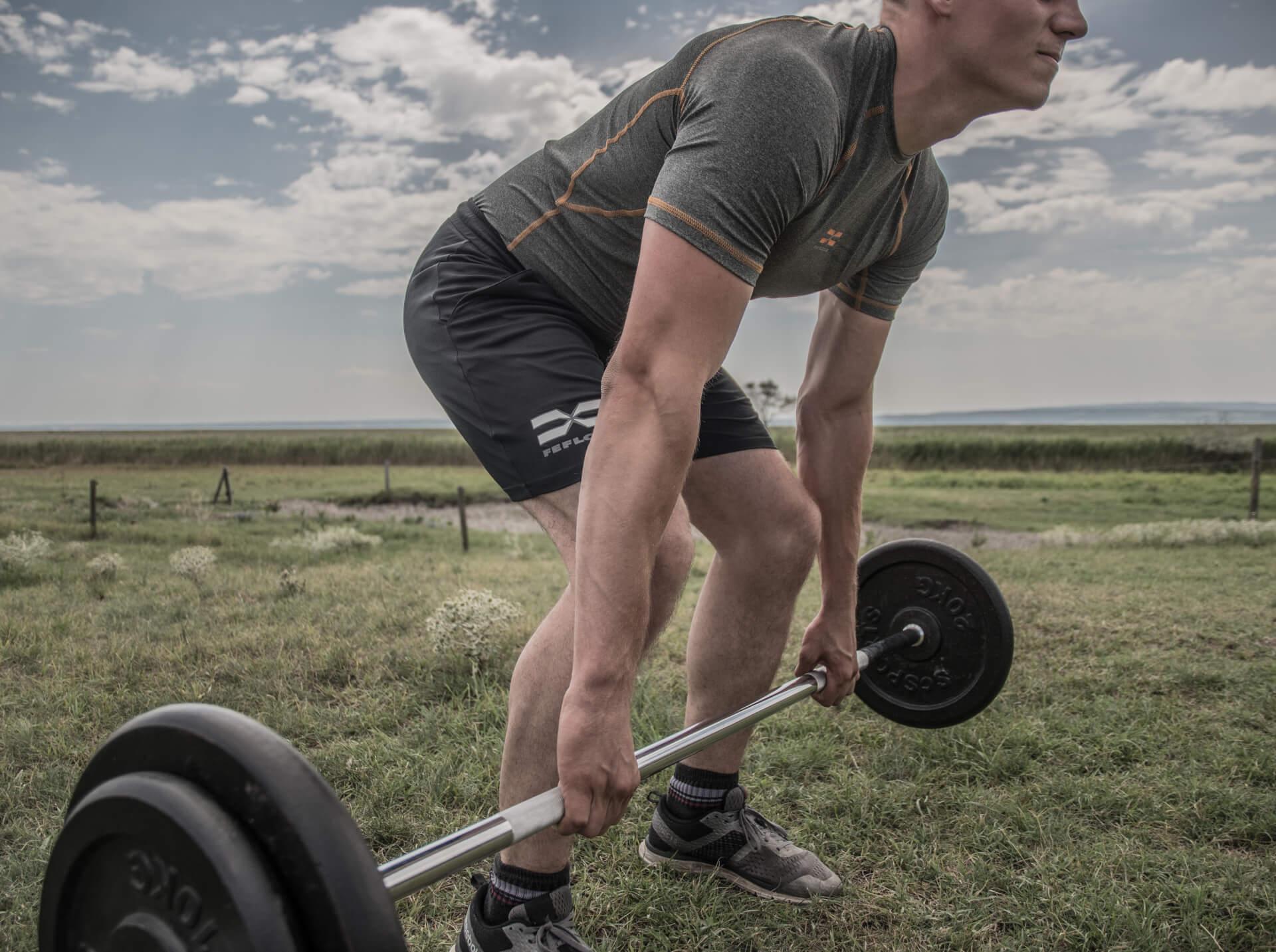Langhantel-Training am See im FEFLOGX Sportswear Rashguard Compression und der Allrounder-Shorts.