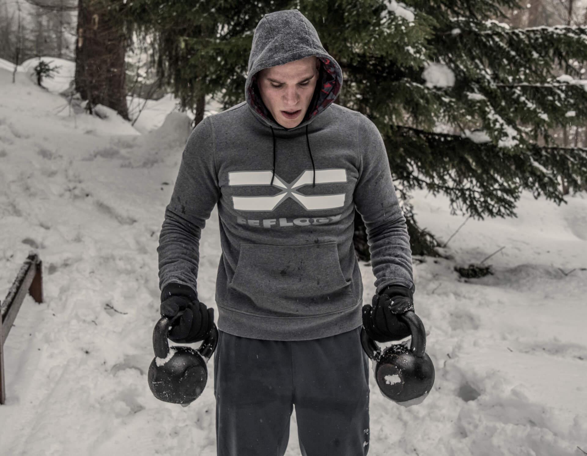 FEFLOGX Sportswear After-Train-Hoodie Winter-Workout mit Kugelhanteln im Schnee.