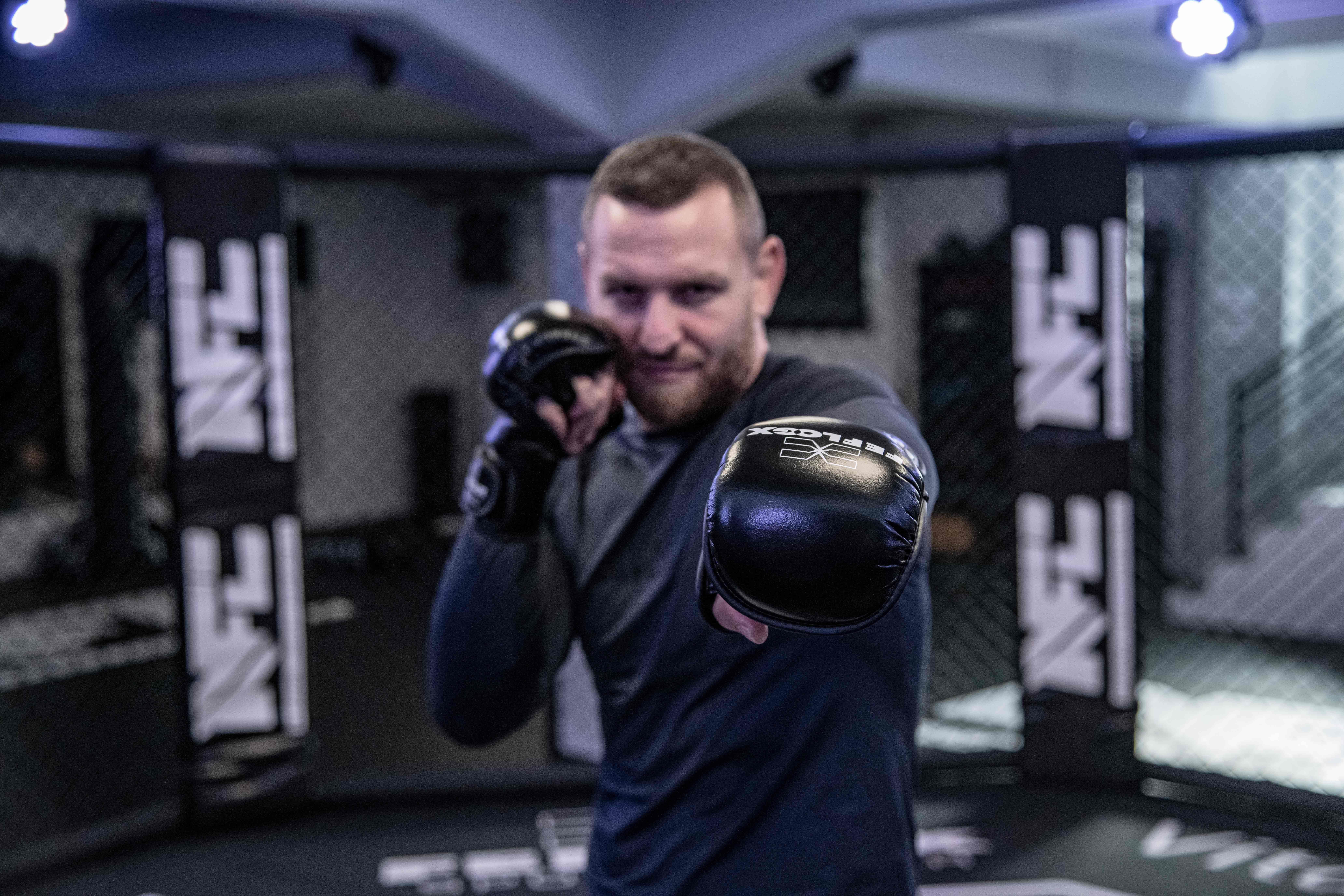 Max Schwindt, Ringer Profi, mit FEFLOGX Sportswear Rashguard lang und MMA Sparringshandschuhen im NFT Cage der NFC in Krefeld.